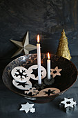 Two lit candles amongst star and snowflake pendants in bowl