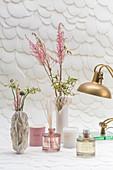 Stillleben aus skulpturalen Vasen und Raumdüften vor Strukturtapete