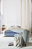 Armchair and box spring bed with blue and white gingham frame in front of long curtains