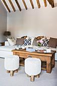 Zwei Hocker vor dem Couchtisch im naturfarbenen Wohnzimmer