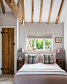 Ländliches Schlafzimmer mit offener Balkendecke