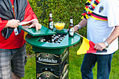 Two men stood at tall table made from beer crates with compartment for beer
