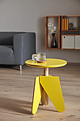 Bright yellow, three-legged stool with threaded rod used as side table