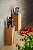 Wooden organiser and knife block on wall panel in kitchen