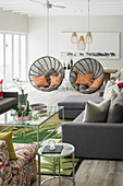 Two round hanging chairs forming partition in open-plan interior