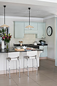 Island counter in kitchen in shades of pastel green and cream