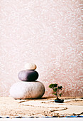 Felt pebbles and a bonsai on sand against pink wallpaper