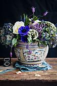 Blau-violettes Blumenarrangement in Porzellanvase vor schwarzem Hintergrund