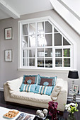 Scatter cushions on white leather couch below interior window in living room