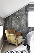 Old armchair against grey wallpaper below sloping ceiling