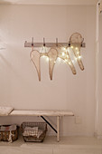 Two pairs of wings and fairy lights hung on coat rack