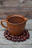 Ceramic jug on trivet handmade from horse chestnuts