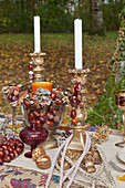 Antique candlesticks and glass goblet decorated with horse chestnuts