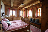 Double bed with red-and-white gingham bed linen in log cabin