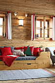 Festive cushions on wooden bed in log cabin