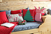Festive cushions and angel cushion on wooden bed in log cabin