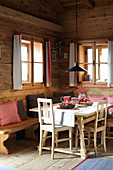 Festively decorated dining table and bench in log cabin