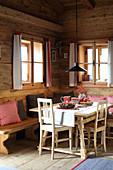 Weihnachtlich dekorierter Esstisch und Sitzbank in einer Hütte