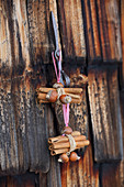 Bundles of cinnamon sticks and nuts hung on rustic wooden door