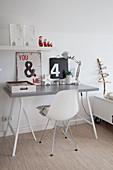 Vintage Schilder und Lampe auf schlichtem Schreibtisch mit grauer Platte und Klassikerstuhl