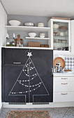 Kitchen cupboards with Christmas tree drawn on chalkboard doors