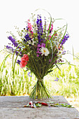 Summer bouquet with delphiniums on garden table