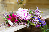 Summer bouquet with phlox and echinacea on wooden bench