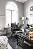 Black-and-white striped armchair in front of arched window in living room