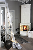 Fire in white tiled stove in grey interior