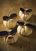 Pumpkins decorated with stick-on mouths and sunglasses