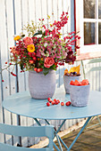 A lavish autumnal bouquet, Chinese lanterns and chestnuts on a garden table