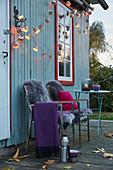 DIY-Lichterkette aus Papierbackförmchen, Plaid und Schaffelle auf Gartenstühlen, Frau im Hintergrund