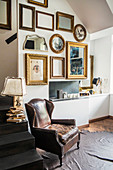 Vintage leather armchair on animal-skin rug, table lamp on steps and various picture frames on wall