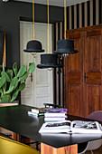 Pendelleuchten mit Zylinder als Lampenschirm über Tisch mit schwarzer Tischplatte