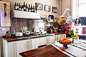 Schale mit Orangen und Blume auf Tisch, darüber Pendelleuchten mit Teekannen als Lampenschirm in einer Küche