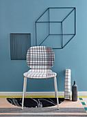 Stuhl mit kariertem Klebefolie überzogen und Würfelform aus Metall an der Wand