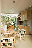 Rattan chairs around dining table in front of open-plan kitchen in conservatory
