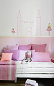 Washi-tape castle on wall above bed with pink scatter cushions