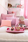 Dolls' tea set on tray and doll on bed with pink scatter cushions