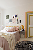 Collage of pictures above bed in feminine bedroom