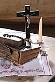 Alte Bücher, Kruzifix, Rosenkranz, Glas und Kerze auf Holztisch