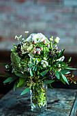 Festive posy of roses, berries, eucalyptus and daisies