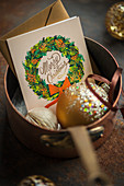Christmas card and Christmas bauble in saucepan