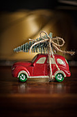 Christmas arrangement of toy car with Christmas tree on roof