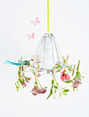 Flowers clipped to lampshade with clothes pegs