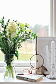 Book, glasses, vase of white flowers, dream catcher and candles on windowsill