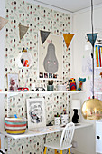 Modular shelving and desk on patterned wallpaper in child's bedroom