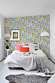Vintage-style floral wallpaper on accent wall in small bedroom