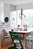Grüner Kinderstuhl am Esstisch mit Retrostühlen am großen Fenster