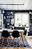 Table and classic chairs in dining area with black walls